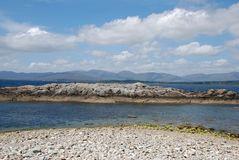 Beach sea rocks and  mountains Stock Images