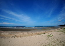Beach sea scene view with deep blue sky and brown beach sand and stones Royalty Free Stock Image