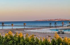 View of the hotel's recreation area on the beach and the sea shore, palm trees under the blue sky of a sunny day royalty free stock photography