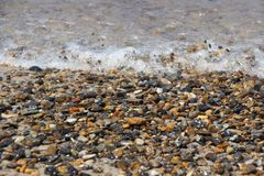Pebbles in the surf zone with a wave washing in stock photo