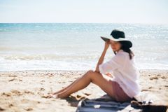 Beach and sea waves focus and blurred hipster girl in hat sitting on beach and tanning. Summer vacation. Happy boho woman relaxing. And enjoying sunny warm day royalty free stock photos