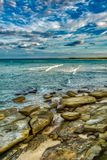 Beach seascape with aged old rocky surface, soft waves and clouds surfers in the distance. Sunshine Coast Australia stock image