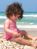 Beach of seashells. A Beautiful little girl sitting on the beach Royalty Free Stock Photography