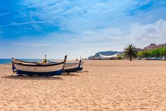 Beach at seaside in Calella in Catalonia, Spain near Barcelona. Scenic old town with sand beach and clear blue water. Famous. Tourist destination in Costa Brava stock photography