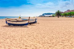 Beach at seaside in Calella in Catalonia, Spain near Barcelona. Scenic old town with sand beach and clear blue water. Famous. Tourist destination in Costa Brava royalty free stock images