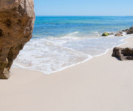 Secluded white beach. Beach secluded by rocks on a blue sky day Stock Images