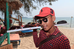 Beach seller boy of sunglasses on coastline Royalty Free Stock Image
