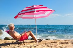 Beach senior man under parasol royalty free stock photos