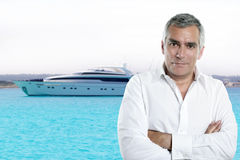 Beach senior tourist summer vacation white shirt. Millionaire senior posing in front a luxury yacht during summer vacation stock photos
