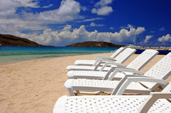 Beach Serenity. Empty white recliner chairs lined up in a row along a sandy beach in the British Virgin Islands royalty free stock photography