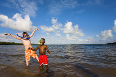 Beach Series - Diversity. Two young boys playing with Snorkel Gear in the ocean - one African American, one Caucasian. John Pennecamp Park, Florida Keys Stock Photos