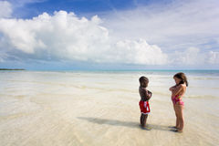 Beach Series - Diversity. Two young children glaring at each other on the beach - an African American boy and a Caucasian girl. Bahia Honda, Florida Keys Stock Photo