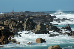 Beach Series: Fishing on the R. Waves crashing in and fishermen on the rocks stock photography