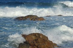 Beach Series: On the Rocks. Waves and small rocks creating foam stock image