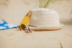 Beach set hat and sunscreen lotion lying on sand Stock Images