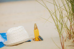 Beach set hat and sunscreen lotion lying on sand Stock Photography