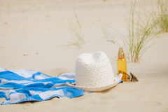 Beach set hat and sunscreen lotion lying on sand Royalty Free Stock Photo