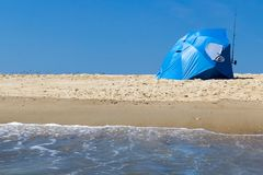 Beach shade tent. Blue umbrella and surf fishing rod Royalty Free Stock Image