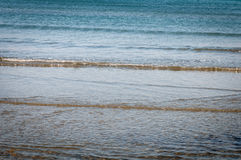 Beach with shallow water and small waves. Royalty Free Stock Image