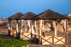 Beach shelters. For tourists with sunbeds and tables Royalty Free Stock Image