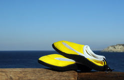 Beach Shoes Against Sea Background. Yellow beachshoes against the background of the dark blue sea and light blue sky Royalty Free Stock Photos