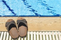Beach Shoes. A pair of mens leather sandals by side of swimming pool stock images
