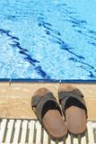 Beach Shoes. A pair of mens leather sandals by side of swimming pool stock photography