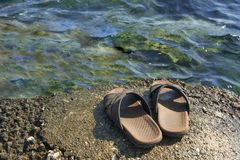 Beach Shoes. A pair of mens leather sandals on water's edge by sea stock photo