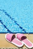 Beach Shoes. A pair of womens plastic sandals by side of swimming pool stock images