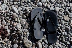 Beach shoes on pebble beach Royalty Free Stock Photo