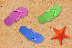Beach shoes and starfish over yellow sand background Stock Image