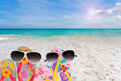 Beach shoes with sunglasses on tropical sea and sky background. Stock Photo