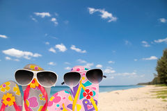Beach shoes with sunglasses on tropical sea and sky background. Royalty Free Stock Photo