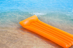 Beach shore with orange floating lounge and waves Royalty Free Stock Photography