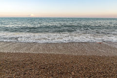 Beach Shore with small stones. Waves on the shore beach with small stones at sunset Stock Photos