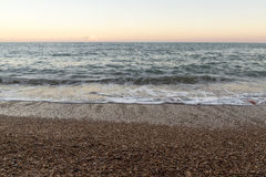 Beach Shore with small stones. Waves on the shore beach with small stones at sunset Stock Image