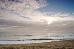 Beach shore. View of sand and sky with sun and clouds Royalty Free Stock Image