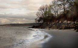 Beach shoreline and clouds. Small sandy beach and rocky shoreline on an overcast and cloudy day stock photography
