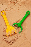 A beach shovel and a beach rake on the sand Royalty Free Stock Photos