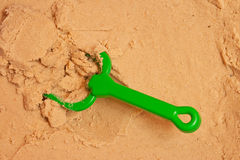 A beach shovel and a beach rake on the sand. Close up Royalty Free Stock Photography