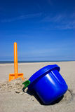 Beach shovel and bucket. Orange plastic spade and blue bucket in the sandy seashore Royalty Free Stock Photo