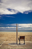 Beach shower with seat for disabled people. Aluminum shower with wooden seat for disabled people; sand beach, sea, horizon and blue sky with white clouds on the Royalty Free Stock Images
