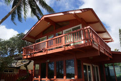 Beach side of Red Beach House with tall coconut tree overhead Royalty Free Stock Photos