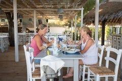 Beach side restaurant. Two women having lunch and chatting in a beach side restaurant stock photography