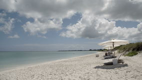 Beach-side view with lounge chairs and umbrellas. A wide panning shot of a white sandy beach with lounge chairs and umbrellas under the blue sky and with clear stock footage