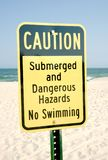 Beach Signs warning people danger ahead. Beach sign on a public beach warning people of dangers ahead royalty free stock photography