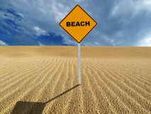 Beach sign on sand dune. Yellow beach sign on rippled sand dune with blue sky Royalty Free Stock Images