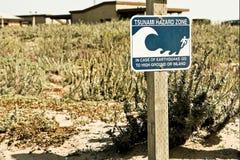 Beach sign states Tsunami Hazard Zone. A warning or caution sign near the beach reads Tsunami Hazard Zone. Tsunamis generally occur following earthquakes royalty free stock photography
