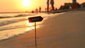 Beach sign and the sunset on the sea, vacation, summertime traveling concept stock video