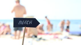Beach sign - tourists and umbrellas on summer hot day and tropical sea stock video footage
